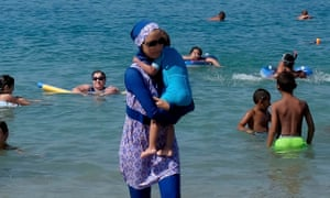 A woman wearing a burkini on a beach in Marseille the day after the country's highest administrative court suspended a ban on full-body swimsuits.