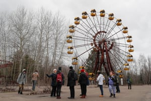 Tourists standing in front of carousel in Pripyat