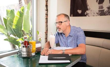 Sam Bain, co-writer of Peep Show, drinking a milkshake at a table