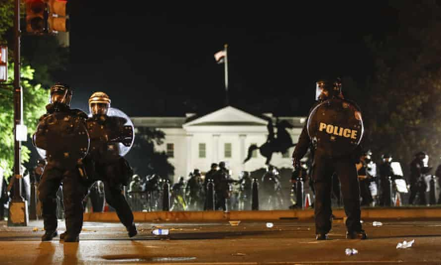 Police stand on H Street in Washington DC as demonstrators protest the death of George Floyd