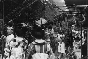 Kuwabara captured a world of contrasts. In this image, two Geishas make their way through a traditional flower market in Asakusa Koen 1937, catching the eye not only of the photographer but also a vendor