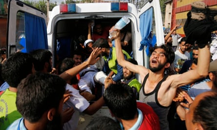A Kashmiri Muslim protester shouts slogans as an injured man is carried from an ambulance to a hospital in Srinagar, summer capital of Jammu and Kashmir.