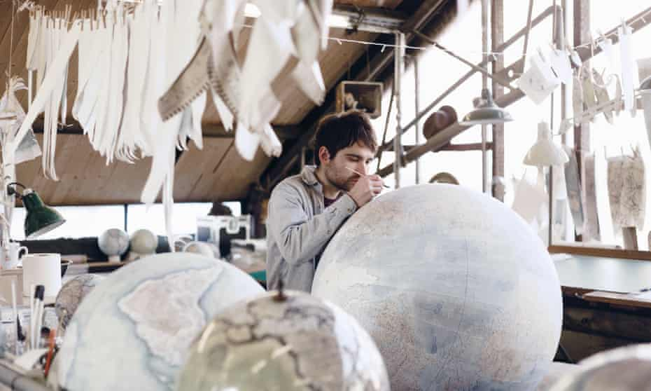 A globe-maker at work on a large globe of the world at Bellerby and Co in north London, UK.