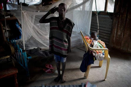 Timon Kamis, 10, salutes like a soldier in the shelter he shares with his family in Malakal, South Sudan.