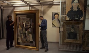 Staff at Tehran Museum of Contemporary Art inspect Picasso's famous work – Window to Paris. In the background a painting by an Iranian artist of Ayatollah Khomeini is displayed on the wall.