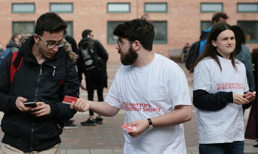 Two people in Labour party T-shirts handing a card to another student