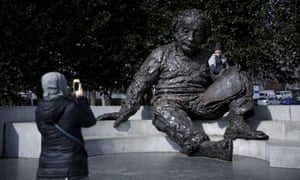 A man poses for a picture at the  Albert Einstein Memorial in Washington, D.C.