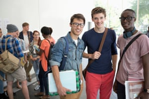 Three smiling male students standing together with other students in backgroundStudents who are socialising at University