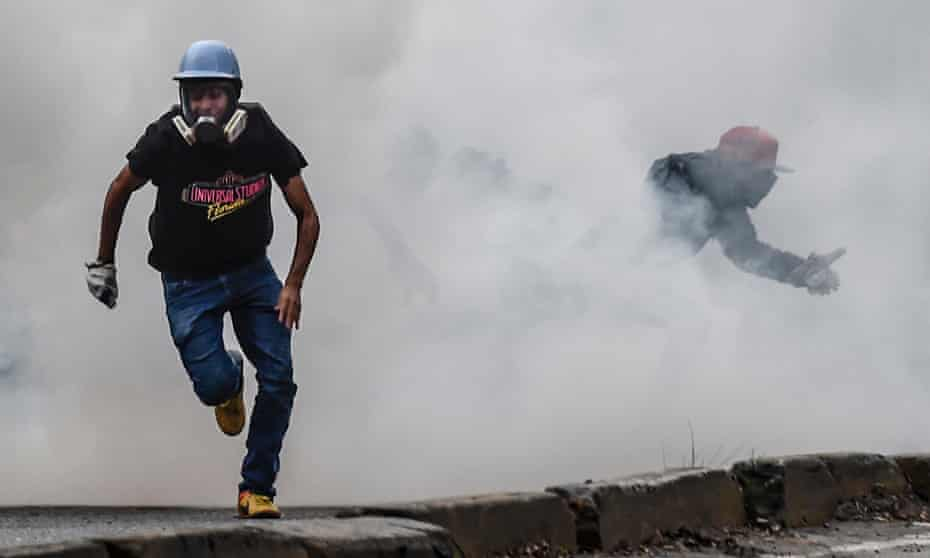 Opposition demonstrators clash with riot police during an anti-government protest in Caracas on 20 July 2017.