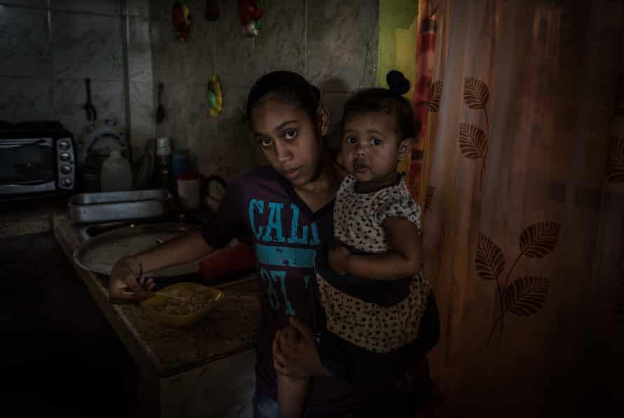 A woman gives food to a girl at a charity-run kitchen for children in Petare
