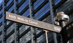 A signpost pointing to an NHS walk-in centre in London