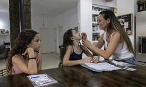 Yifat Kahana takes a swab sample from her daughter, Ariel, 10, for a Covid-19 Antigen test kit ahead of the first day of school, at their home in Moshav Talmey Yafe, Israel.