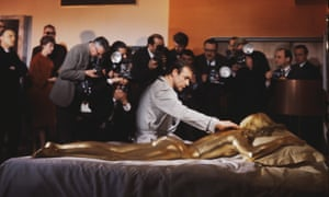 Sean Connery as 007 and a gold-painted Shirley Eaton being photographed on the set of the James Bond film Goldfinger at Pinewood Studios