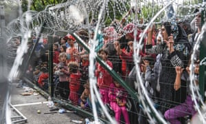 Refugees stand behind a fence on Hungary's border with Serbia.