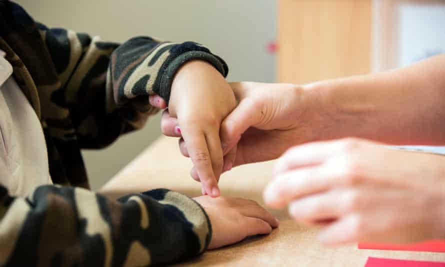 Parent guiding child's hand