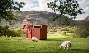 Miner's Legend cabin in a green field against a mountain backdrop. Miner's Legend pays homage to the country's industrial heritage. Architect How About Studio has filled angular spaces with great details and paid close attention to natural lighting. The bed is upstairs and offers great views.