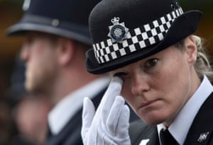 A police officer wipes away a tear outside Southwark Cathedral