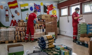 Italian Red Cross volunteers prepare food for distribution to people with financial difficulties in Catania.