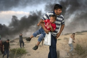 A Palestinian protester carries a boy as he runs from teargas fired by Israeli soldiers during a protest on the beach near the border with Israel.
