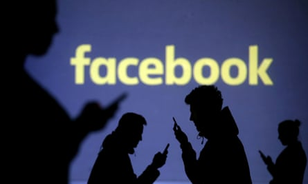 Mobile users next to a screen projection of the Facebook logo.