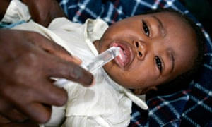 A nurse giving sugar solution to a child suffering from cholera in Zimbabwe in 2009.