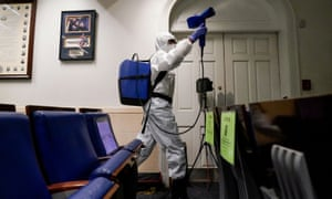 A member of the White House cleaning staff sprays the press briefing room.