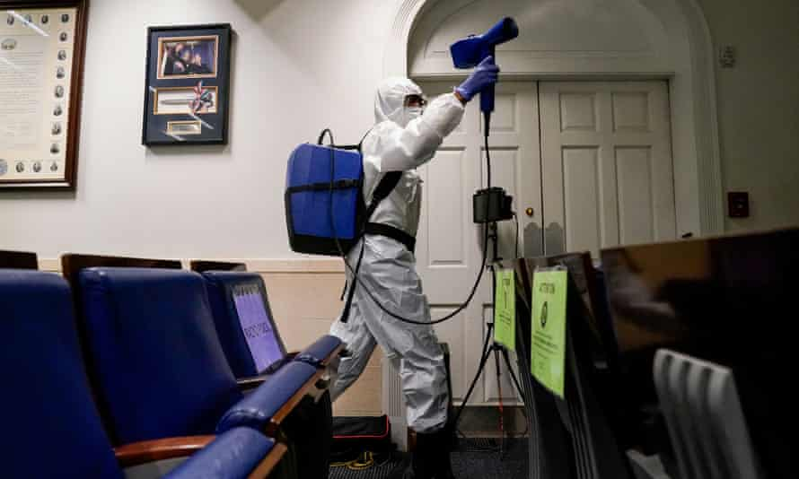 A person wearing a white boiler suit and mask carries a blue backpack and holds a spray attachment as they walk past rows of blue upholstered flip chairs