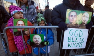 People hold up photographs of NYPD officers Rafael Ramos and Wenjian Liu as the casket of Ramos arrives for his wake.