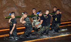 Thai soldiers carry pumping equipment inside the flooded cave complex.