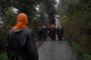 A protester looks at riot police during the eviction of environmental activists from the site of a proposed new airport.