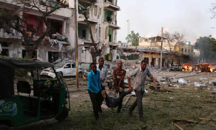 Civilians evacuate an injured man from the area of the car bombing in Mogadishu