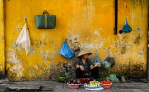 By Ian Webb. Taken in Hanoi, Vietnam, on a street where people were selling fruit and vegetables. I was particularly drawn to this lady as she was on her own and the vibrant yellow wall made for a striking background.
