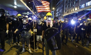 Protesters prepare to confront riot police while waving a US flag