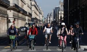 Cyclists ride on the rue de Rivoli in Paris.