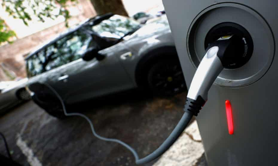 An electric car is plugged in at a charging point for electric vehicles in Rome