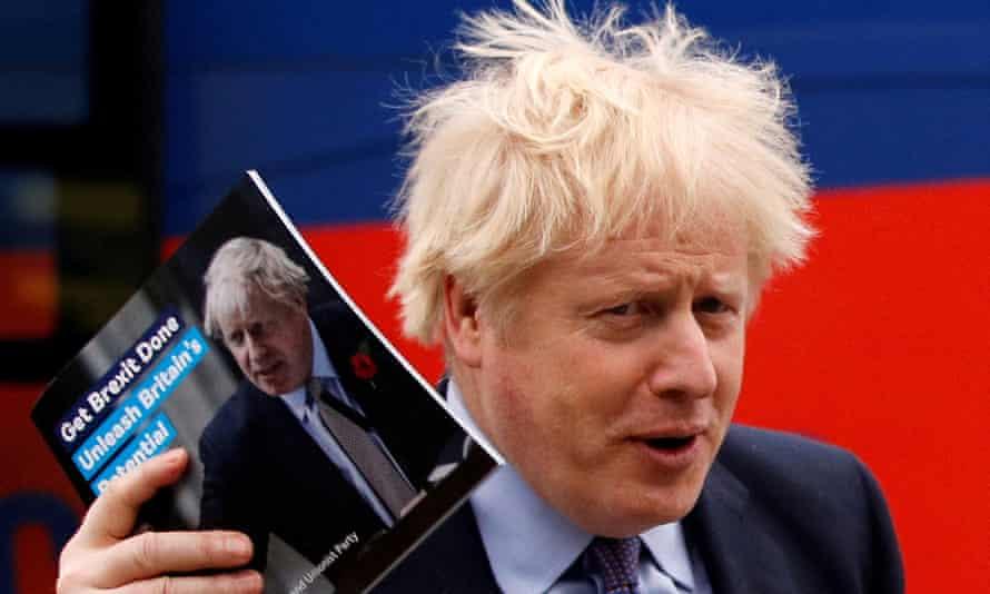 Boris Johnson with the Conservative manifesto in November 2019.