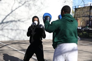 """William Smith (green shirt), 25-years-old, teaches the basics of boxing to Dominick Spies, 21-years-old, in Bedford Stuyvesant, Brooklyn. William: """"I usually go to CKO Kickboxing gym. I'm taking what I learned from there and teaching Dominick. This is our first time doing this outside, but we plan to do it three times a week. I want to space it out to give myself a break. Dominick: """"I had a sudden interest and William was willing to teach me. We grew up together."""""""