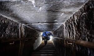 a man walks through the narrow passageway in the bent pyramid in Dahshur , Egypt