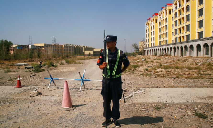 """A Chinese police officer near a """"re-education camp"""" in Xinjiang."""