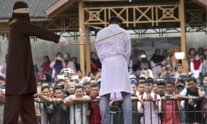A Sharia law official whips a man convicted of adultery with a rattan cane in Banda Aceh.