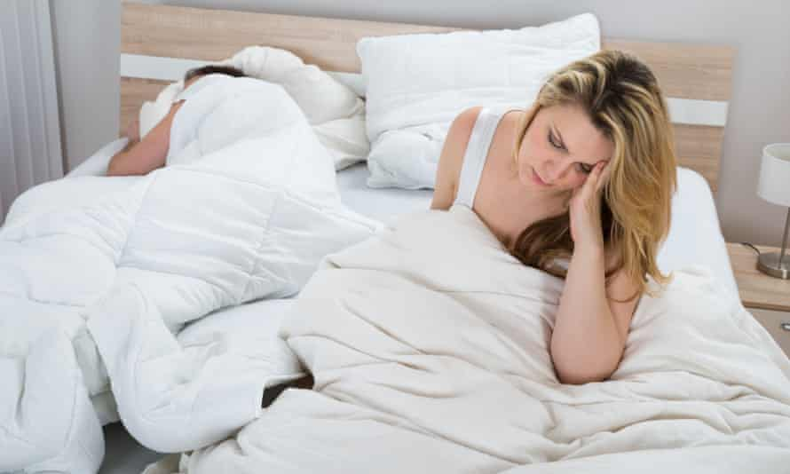 Woman On Bed While Man Sleeping In BedroomUnhappy Woman With Blanket On Bed While Man Sleeping In Bedroom
