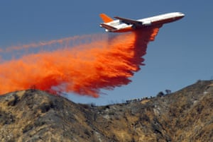 A DC10 airplane tanker dumps fire retardant