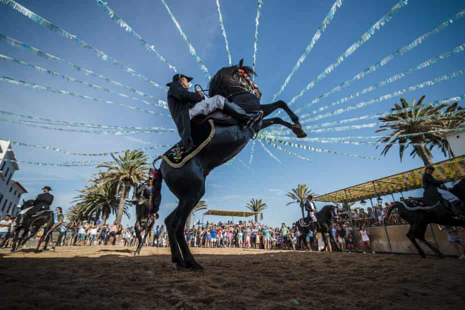 A caixer (horse rider) rears up on his horse during the traditional Sant Antoni festival in Fornells, Menorca.