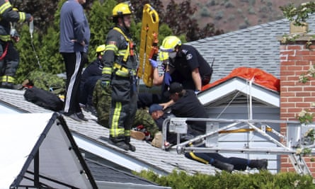 First responders attend to a person on a rooftop at the scene of a crash involving a Canadian Forces Snowbirds airplane in Kamloops.