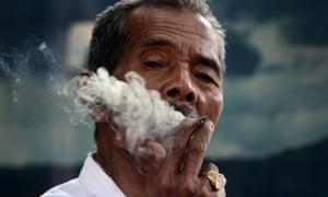 A man smokes a cigarette in Medan, Indonesia
