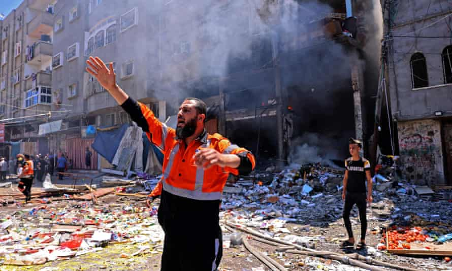 A Palestinian firefighter speaks to colleagues following an Israeli strike on Rafah town in the southern Gaza Strip, on 15 May.