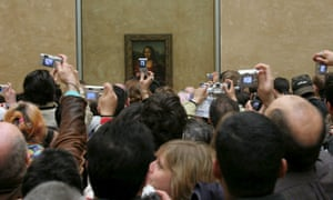 Crowds view the Mona Lisa at the Louvre, Paris.