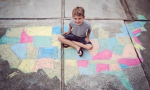 Boy sitting on chalk map of United StatesSix year boy old has drawn map of United States on ground using chalk, sitting on colorful map and smiling.