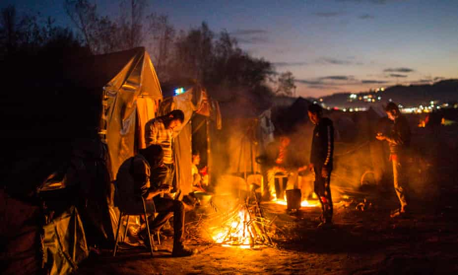 Migrants outside their tents in the Bosnian town of Velika Kladusa, close to the border with Croatia