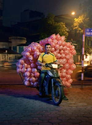 A delivery driver on a motorbike in Hanoi, Vietnam, carrying children's footballs